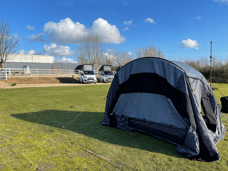 driveaway awning set up with campervans in background